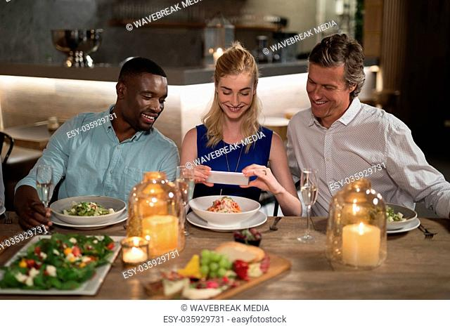 Happy friends taking photo of meal with mobile phone
