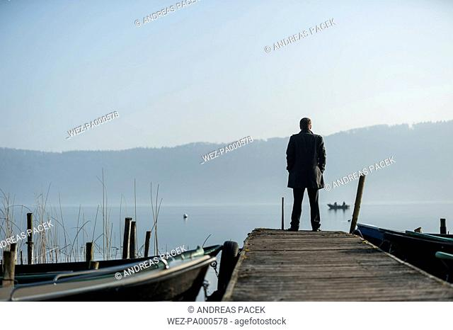 Man standing on wooden boardwalk watching at lake