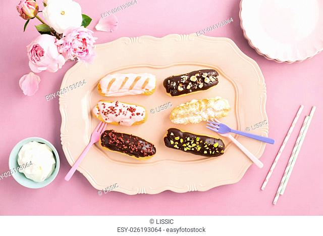 Eclairs with chocolate ganache and icing with different toppings