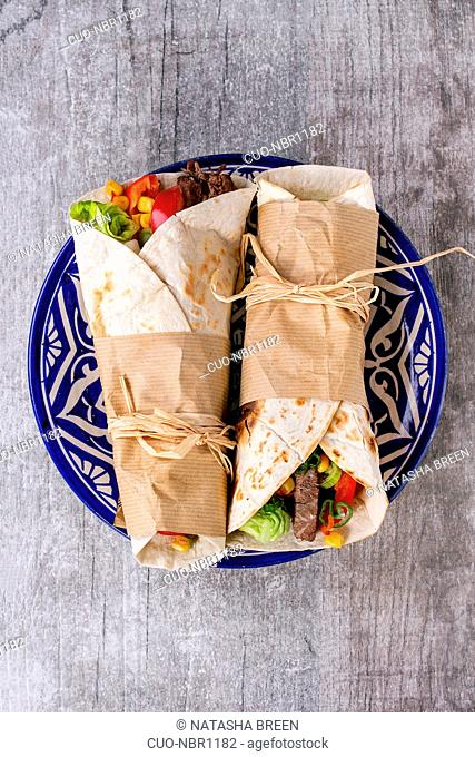 Mexican style dinner. Two papered tortillas burrito with beef and vegetables served on blue ornamental ceramic plate over white wooden background