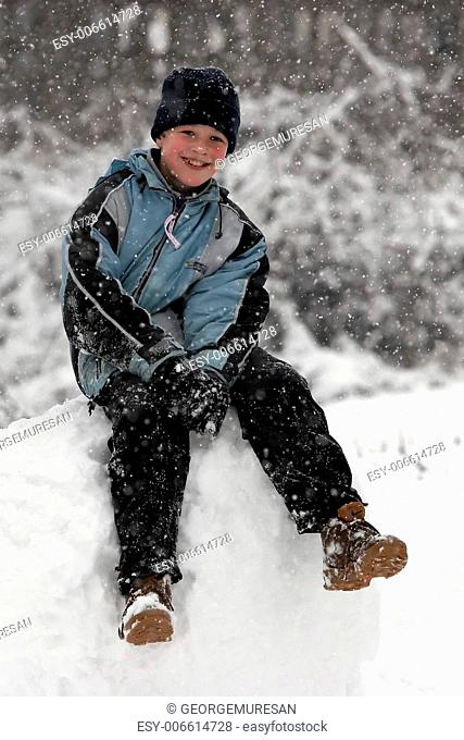 Kid sitting on a snowball