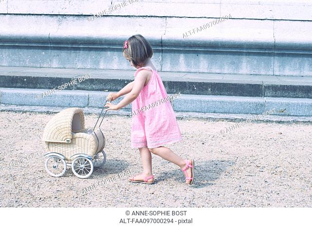 Little girl pushing miniature baby carriage