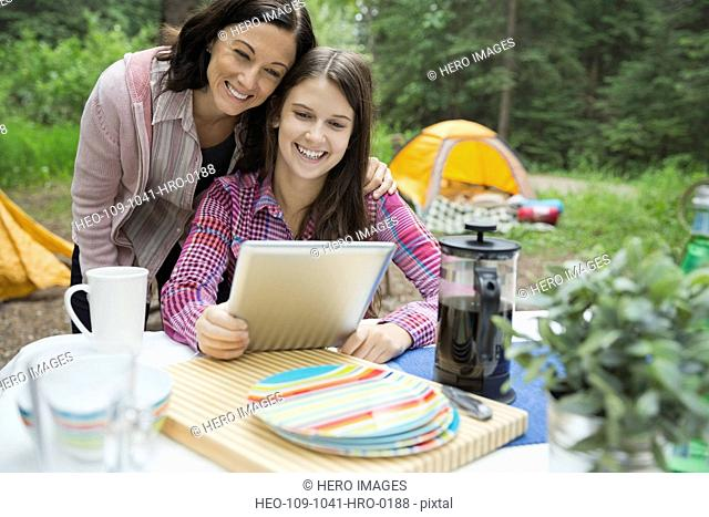 Smiling mother and daughter using digital tablet at campsite