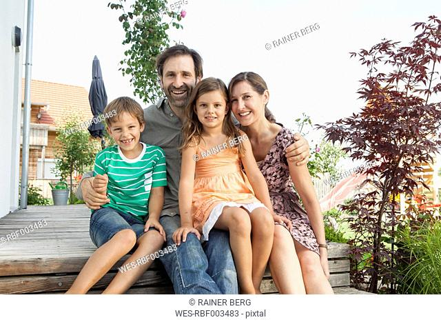 Portrait of smiling family of four sitting on terrace