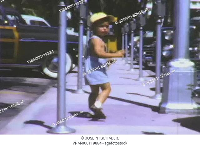 Little boy can't find his car and seems confused in front of parking meters