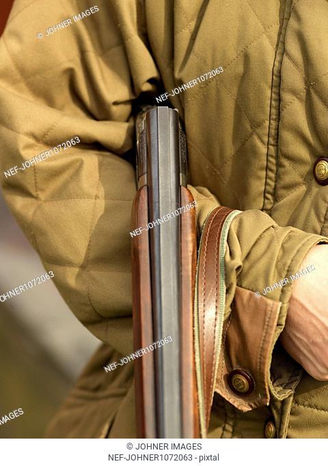 Double-barreled shotgun held by hunter