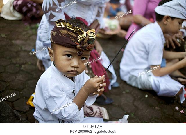 A child sitting with incense at the Kuningan Festival; Bali, Indonesia