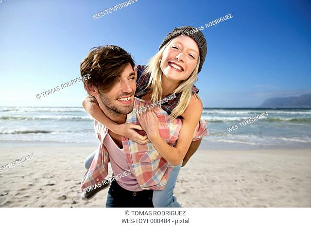 Young man carrying girlfriend piggyback on beach