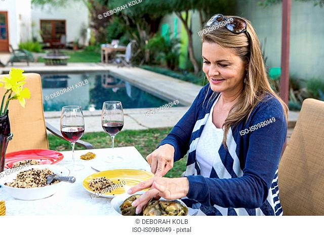 Mature woman serving food at garden table