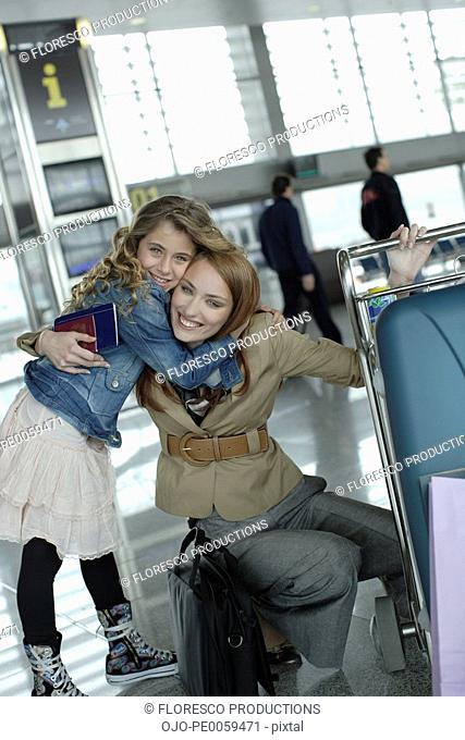 Woman and young girl in airport hugging