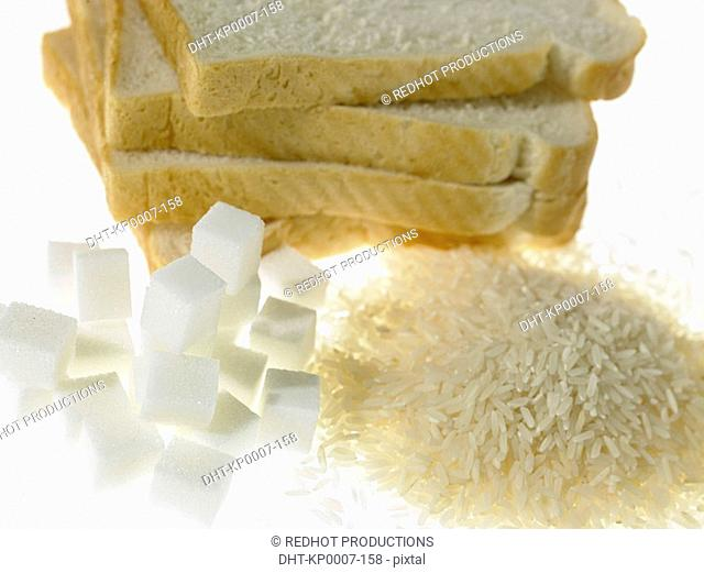 Stack of White Bread slices beside piles of sugar and rice