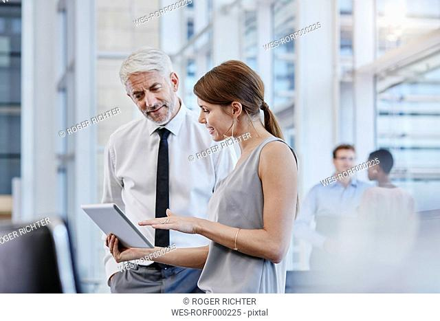 Businessman and businesswoman with digital tablet