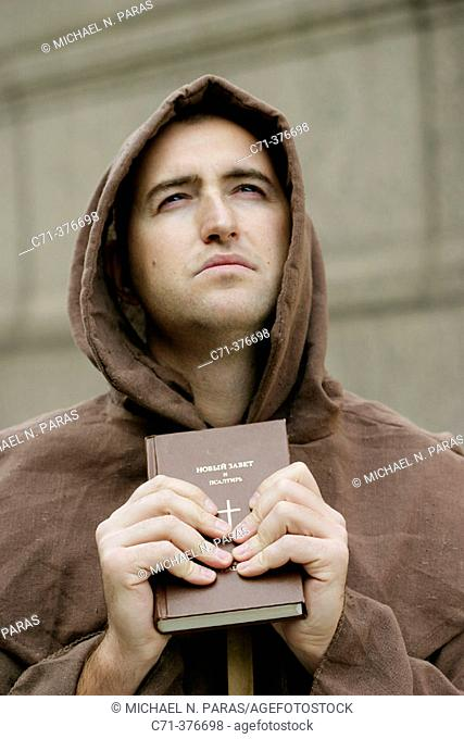 Monk. Priest holding Bible