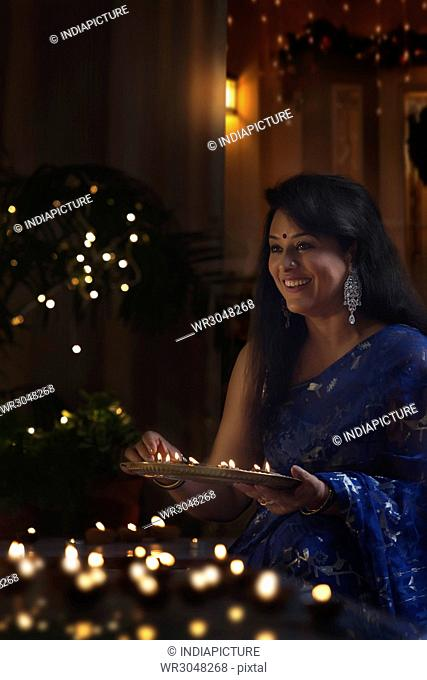 Happy indian woman in traditional sari arranging oil lamp during diwali festival