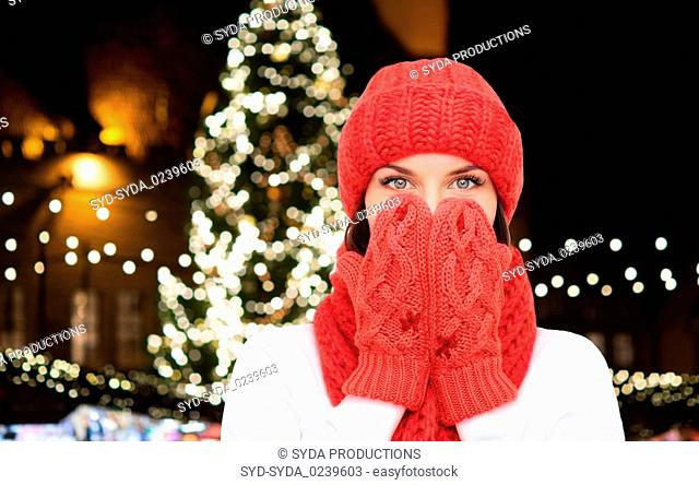 young woman in winter clothes over christmas tree