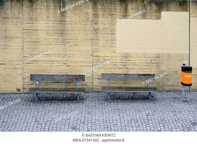 Park benches and an orange rubbish bin standing on a striking concrete wall