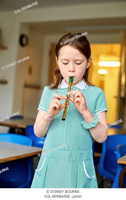 Schoolgirl playing recorder in classroom at primary school