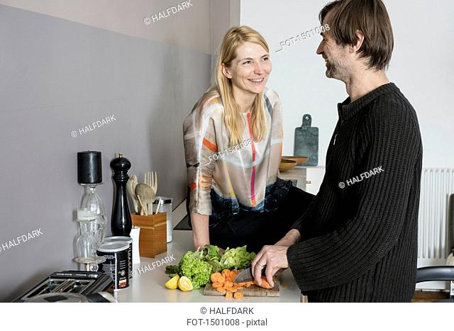 Smiling mature woman looking at man cutting vegetables in kitchen