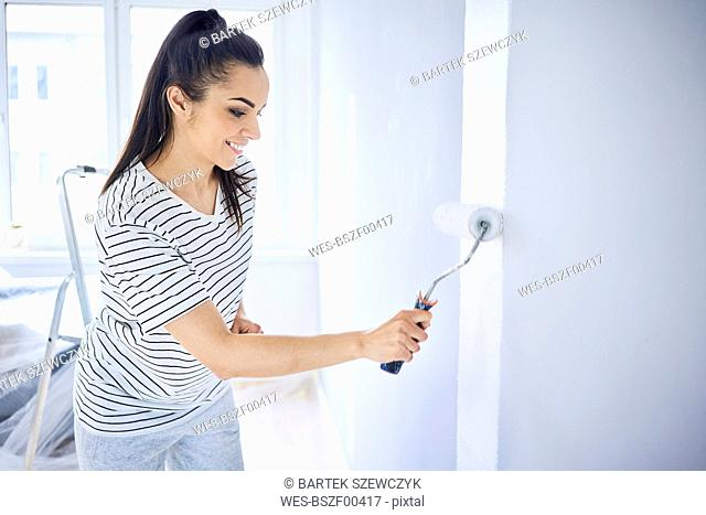 Smiling woman painting wall in apartment