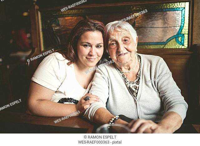 Portrait of smiling senior woman and her granddaughter sitting head to head in a restaurant