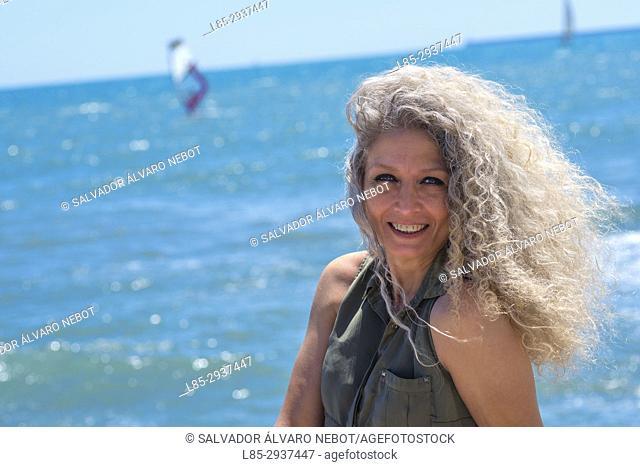 Woman smiling on the Mediterranean coast, Port Saplaya, Contact Us, Spain