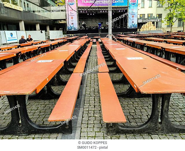Tilburg, Netherlands. Wooden tables and seats in rows prior to a academic student party down town