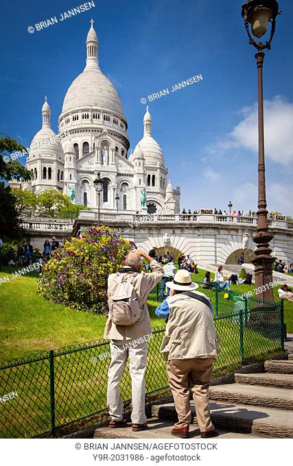 Two photographers below Basilique du Sacre Coeur, Montmartre, Paris France