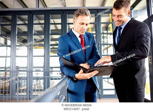Businessmen talking together while looking folder