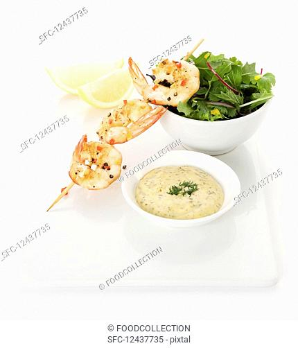 Grilled prawns on a skewer with chilly and pepper, bowl of mixed lettuce, Lemon wedges and tartare sauce with dill topping