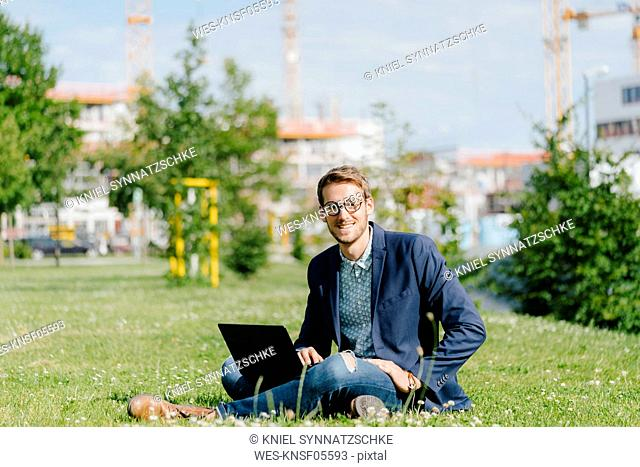 Young businessman sitting in park, using laptop