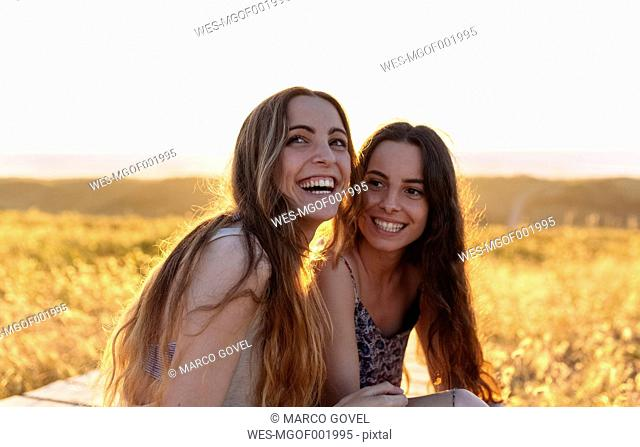 Happy young women sitting on the beach