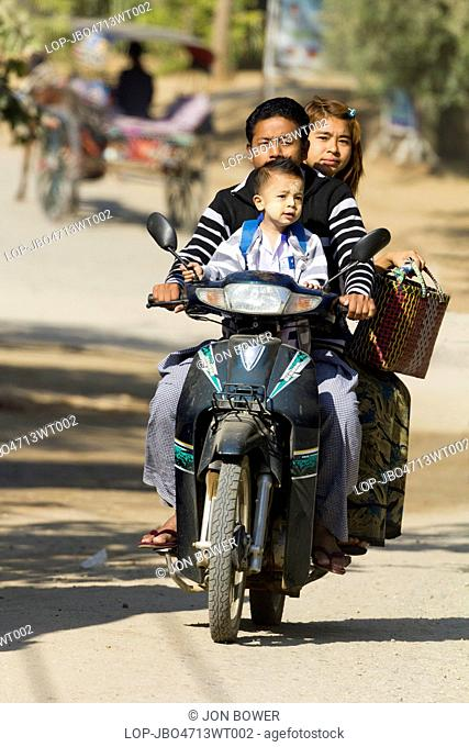 Myanmar, Mandalay, Bagan. A whole family riding on a moped in Bagan in Myanmar