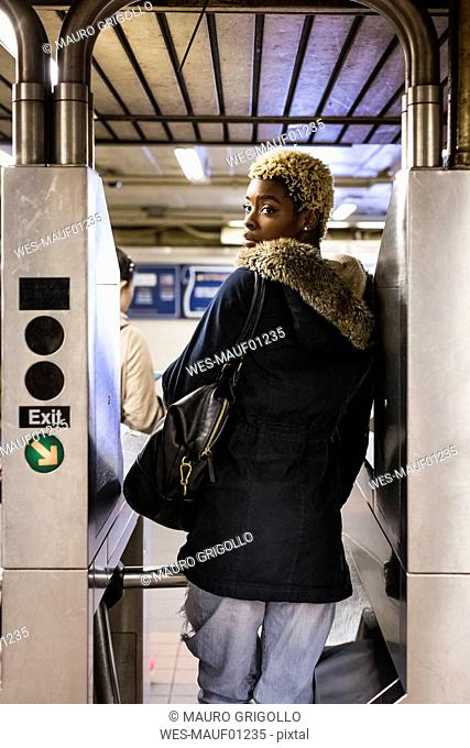 USA, New York City, young woman passing through barrier in subway station