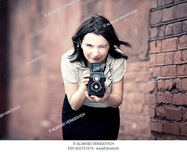 Woman with vintage camera in hands against blurred vintage brick wall background. Pretty young woman taking photo outdoors