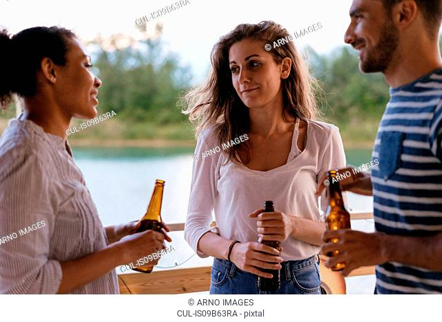 Three friends outdoors, in conversation, holding bottles of beer