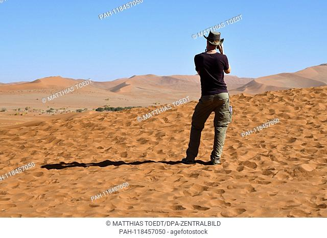 A single tourist takes pictures of the last dune in Dead Vlei, taken on 01.03.2019. The Dead Vlei is a dry, surrounded by tall dune clay pan with numerous dead...