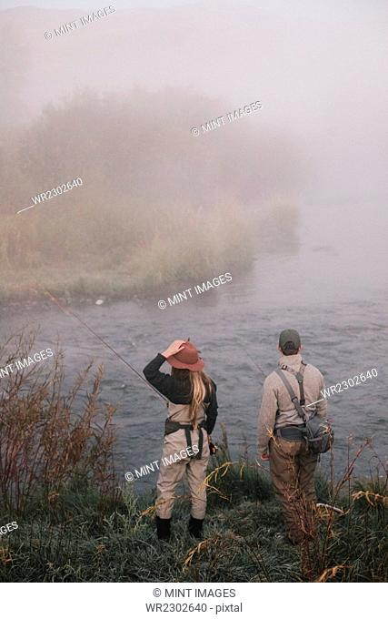 Two people, man and woman standing on the riverbank looking across the water
