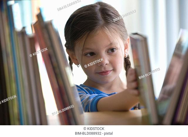 Caucasian girl taking book from shelf