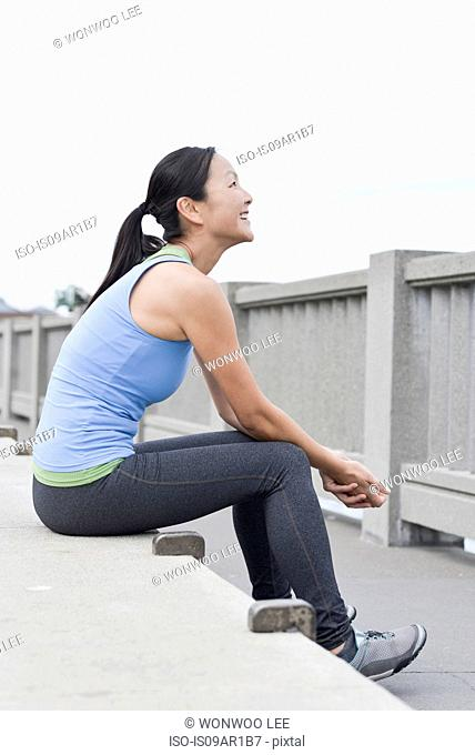Female runner taking break on bridge, San Francisco, California