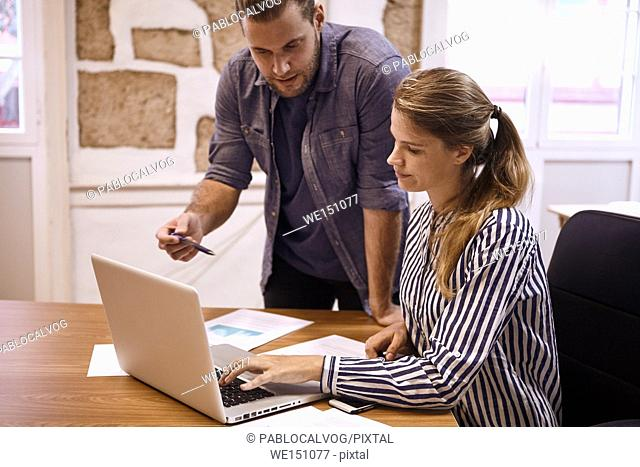 Young business man with a pen in his hand explaining something to the lady while she is typing on the laptop they are sharing
