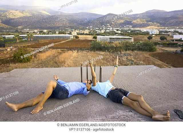 Two young men lying on rooftop, in holiday destination Malia, Crete, Greece