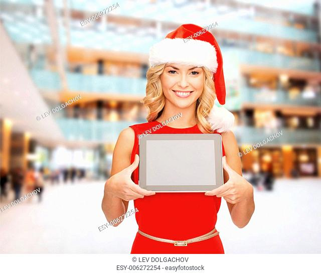 christmas, technology, present and people concept - smiling woman in santa helper hat with tablet pc computer showing blank screen over shopping center...