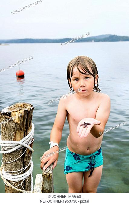 Boy on jetty holding starfish