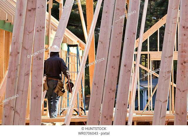 Carpenter with a nail gun at a house under construction