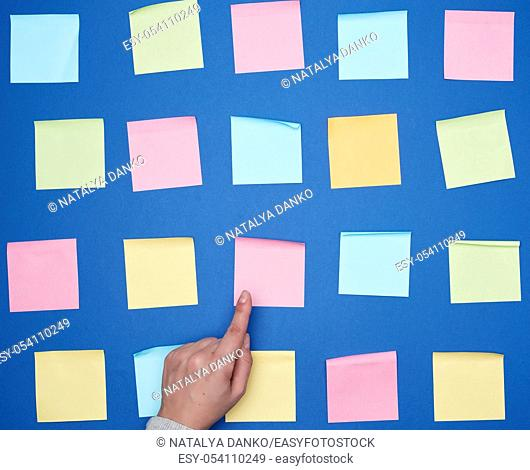 female hand and a lot of empty paper multi-colored square stickers on a blue background, concept of choosing a strategy with the specified finger