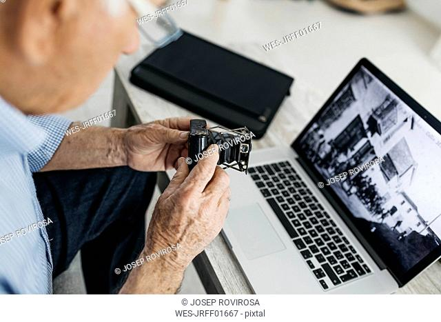Senior man using laptop and holding his old photo camera, screen with old photo