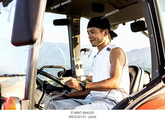 Portrait of Japanese farmer driving red tractor