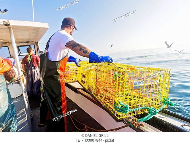 Three fishermen working on boat
