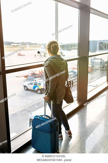 Spain, Asturias, woman waiting to boarding with her suitcase in the airport