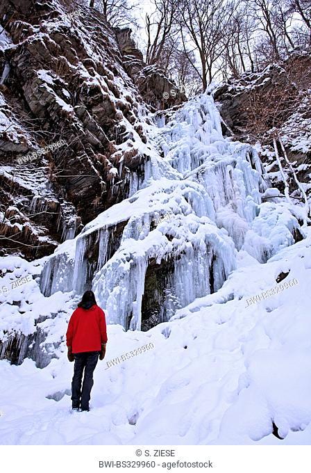 one person looking at the frozen waterfall Plaesterlegge, Germany, North Rhine-Westphalia, Sauerland, Bestwig